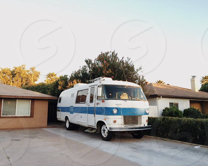 white and blue RV on driveway photo