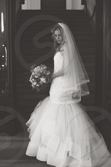 woman in wedding dress standing beside stairs during daytime in greyscale photography photo