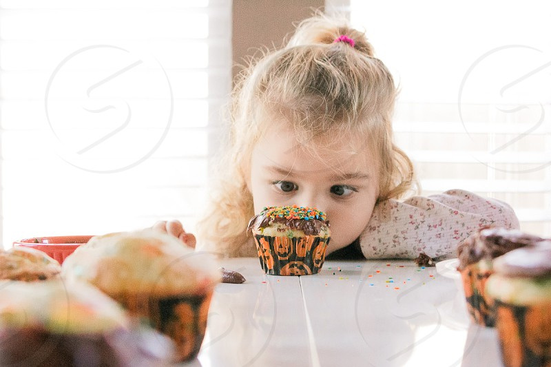 fall halloween cupcakes sprinkles decorating icing chocolate eating child minor girl party photo