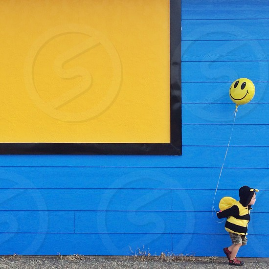 child in black and yellow bee costume holding a smiley yellow balloon photo
