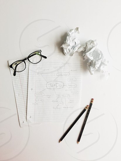 2 white lined papers with to do sketch between black framed eyeglasses and 2 black pencils next to 2 white crumbled papers photo