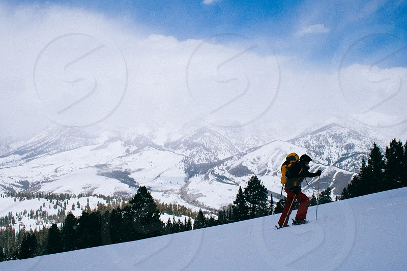 A skier skins up a ridge with the Smokey Mountains in the background in Idaho photo