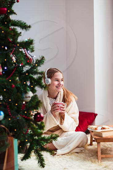 Young girl listening to Christmas carols through her headphones in the early morning photo