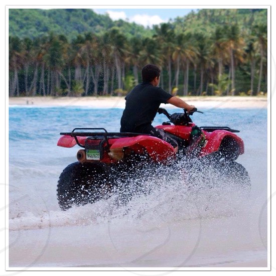 man in black t shirt riding red and black atv photo