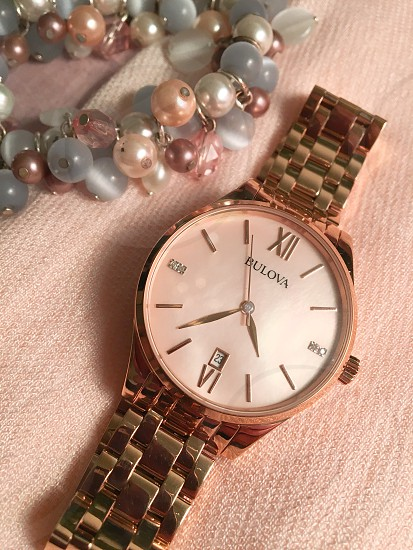 gold link bracelet round bulova analog watch at 4:37 photo