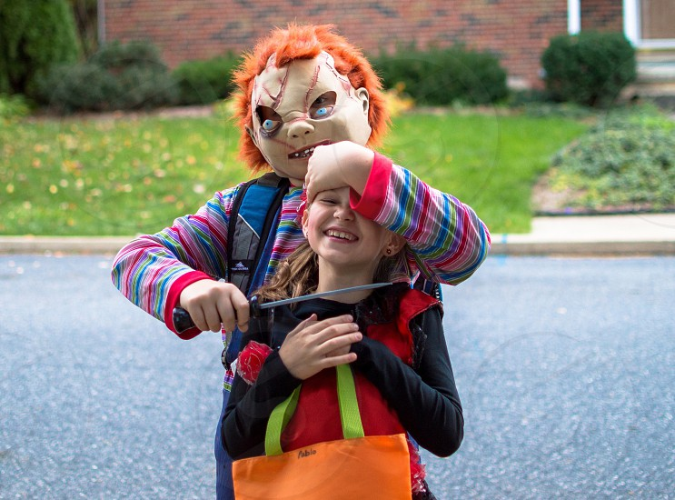 girl being hostage by chucky doll photo