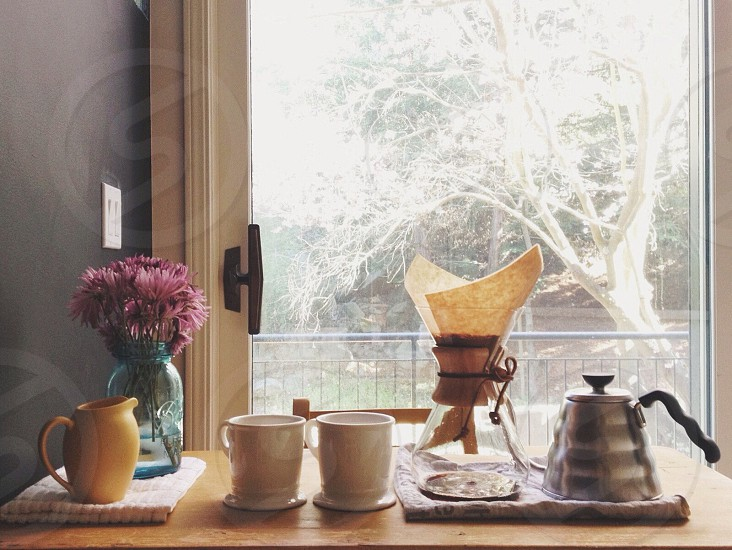 two white ceramic mug on top of wooden table photo