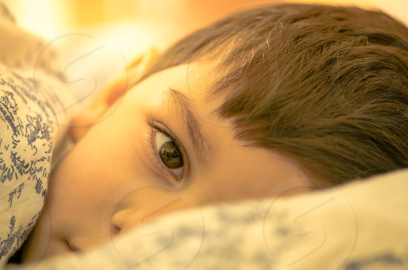 cozy comfort bed morning light covers waking-up awake cold warm home nap-time boy toddler young child face portrait hair eye view warmth photo