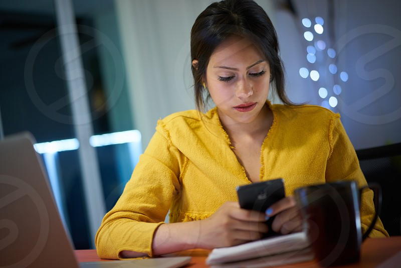 Young woman using smartphone while doing homework at night. Female college student studying and texting with mobile telephone at home. photo