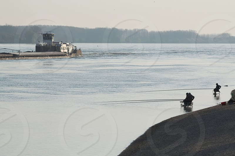 Cargo Ship on the Danube River and Fishermen in the Water photo