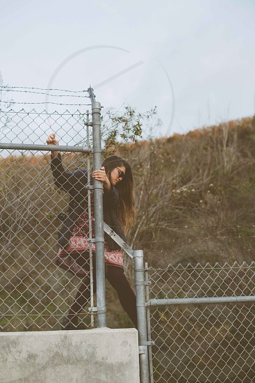 woman climbed on chain link fence photo