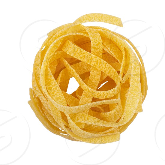 one nest raw tagliatelle italian pasta isolated on white background top view photo
