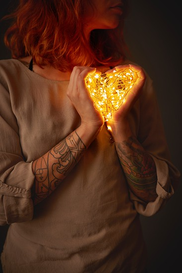 A young girl is holding yellow garland lights in the shape of a heart. St. Valentine's Day photo