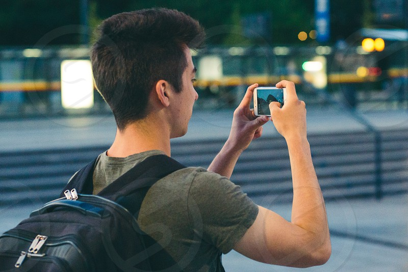 Young man with backpack taking photos using a smartphone in the city at night photo