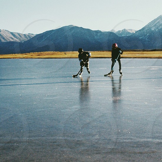 two people playing ice hockey on icy surface photo