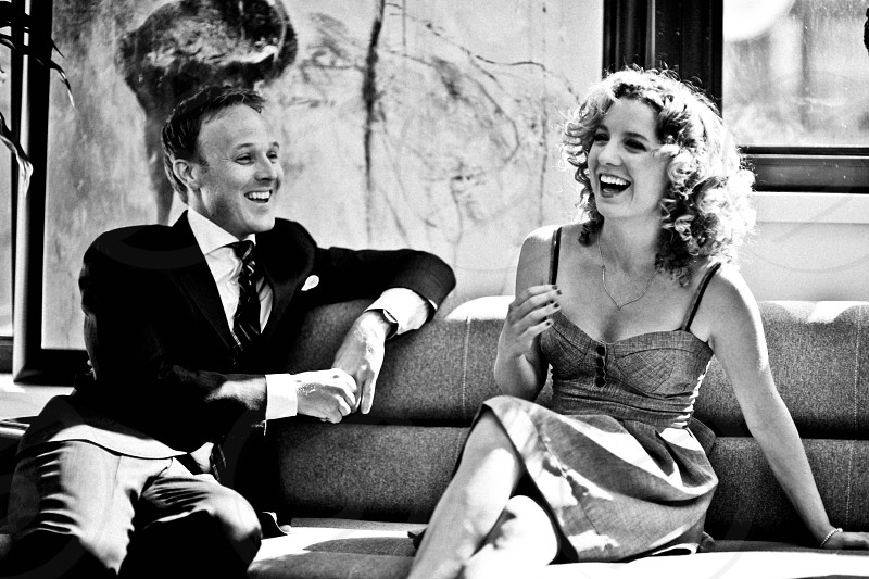 woman sitting and laughing together with man in suit in grayscale photography photo