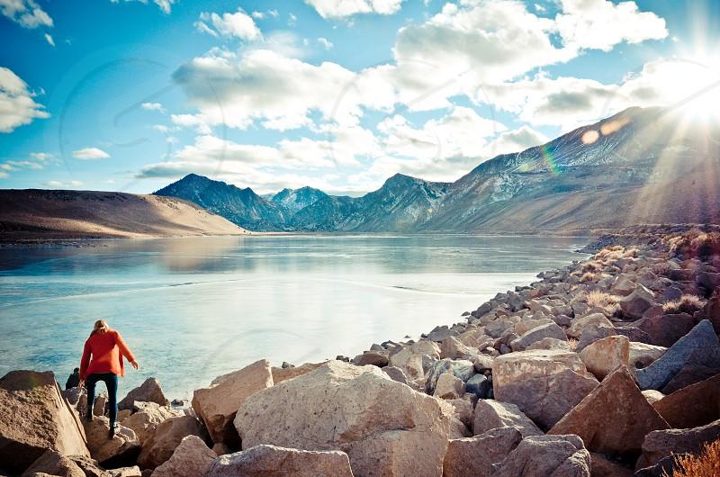 girl explore explorer wanderlust travel mountains sun flare frozen lake sierra nevadas photo