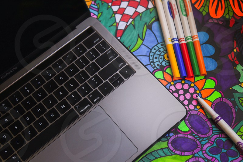 Apple MacBook Pro along side art supplies and a colored in drawing. photo
