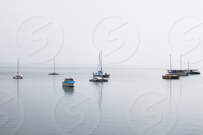 Boats moored in the dead calm of a grey tropical lagoon with reflections of masts in the water. photo