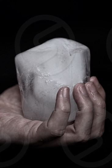 left human hand holding a block of ice photo