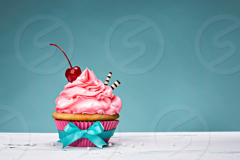 Cupcake with pink buttercream icing and a cherry on top. photo