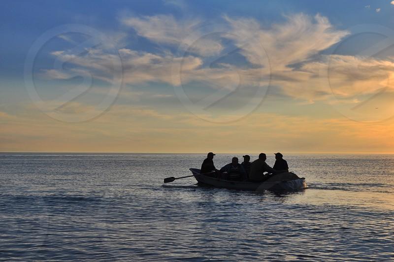 people riding on white rowboat photo