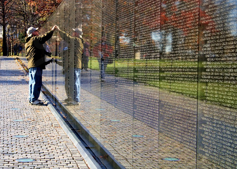 A man touches the Wall of the Vietnam Veterans Memorial wall as he finds the name of a friend with whom he served. photo
