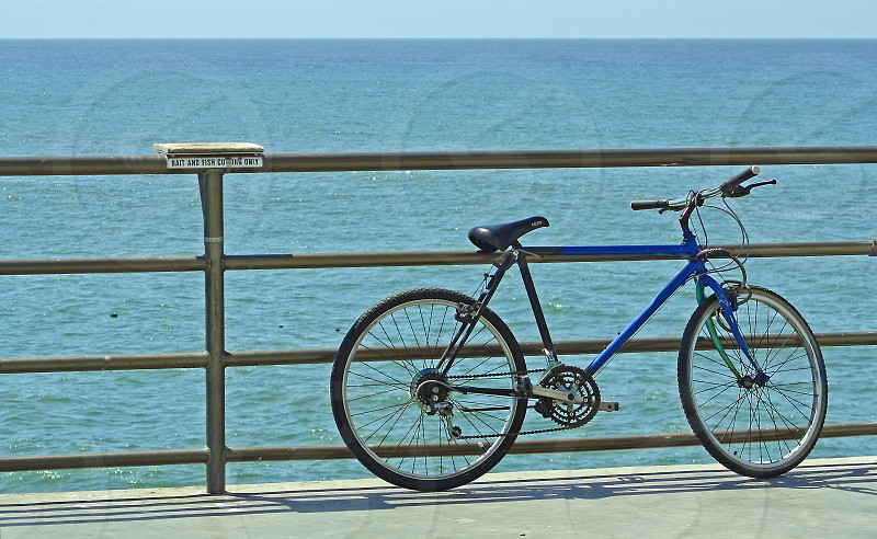 Bicycle leans against the rail of a pier over the ocean photo