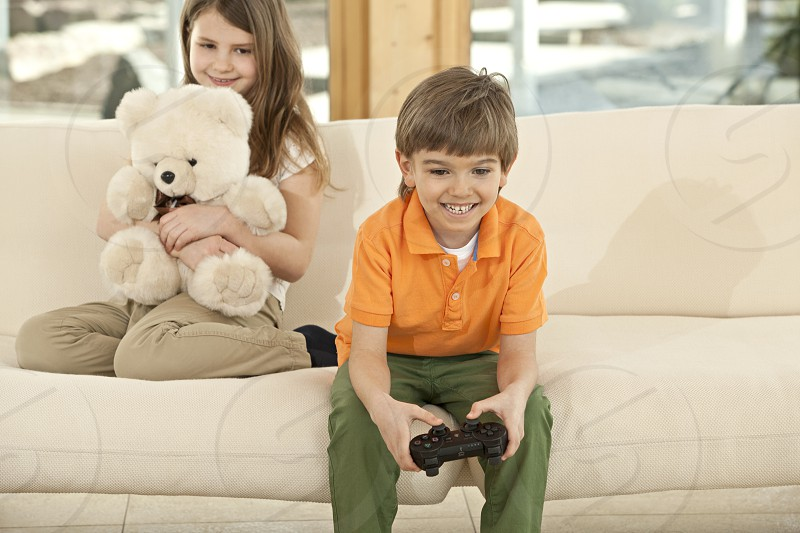 Cute little boy playing video with his sister sitting in background with teddy bear  photo