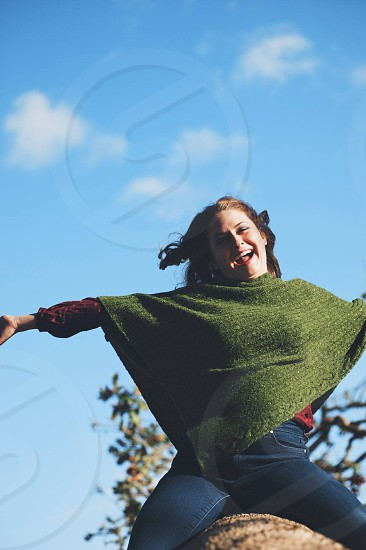 woman in blue jeans and moss chenille poncho on rock smiling blue sky photo