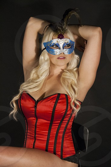 Blonde female wearing a red corset and blue masquerade mask posing with her arms held behind her head.  photo