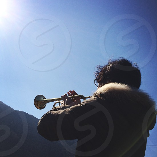 man in brown fur jacket playing trumpet under clear blue sky photo