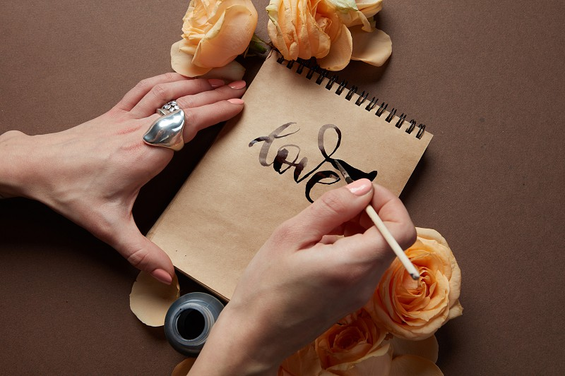 Closeup of female's hand writing word love in diary or notebook in Valentine's Day. Notebook represented on brown background with orange flowers. photo