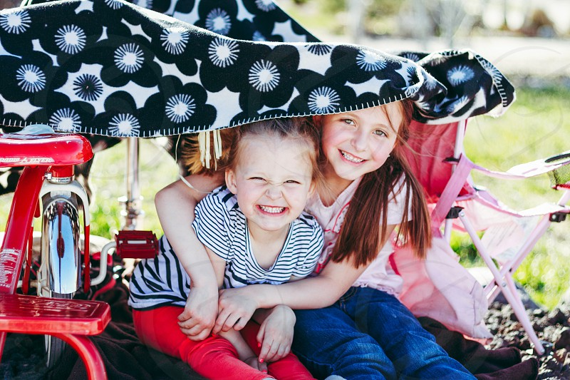 2 girl sitting under tent on green grass photo