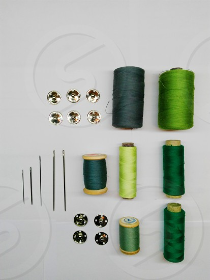 7 different shades of green thread with needle and buttons photo