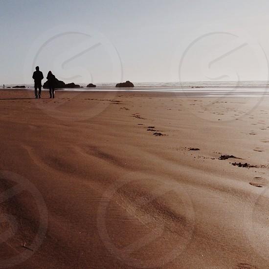 man and woman walking along seashore photo