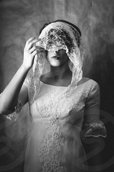 woman in floral scoop neck elbow sleeve dress with lace veil in grayscale photo