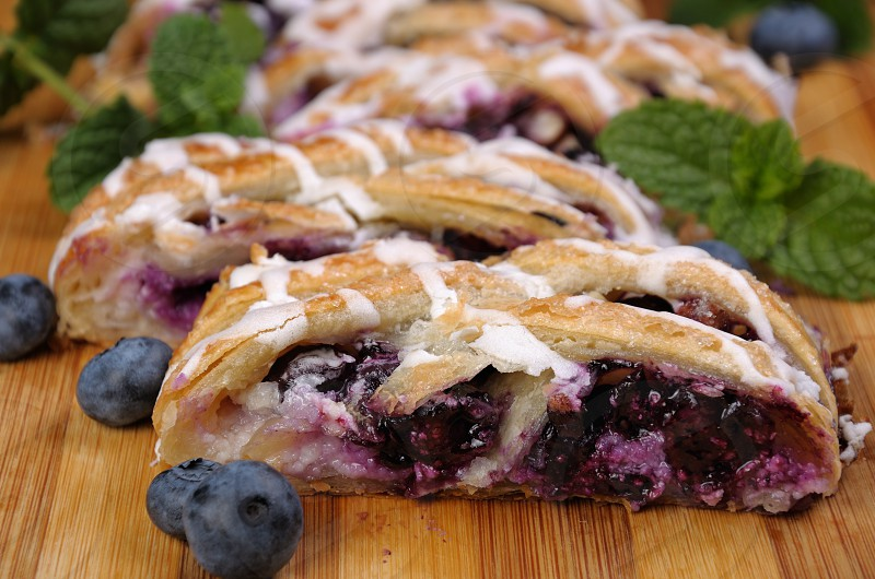 Pie stuffed with cheese cream  blueberry crushed peanuts dough  braided plait  photo