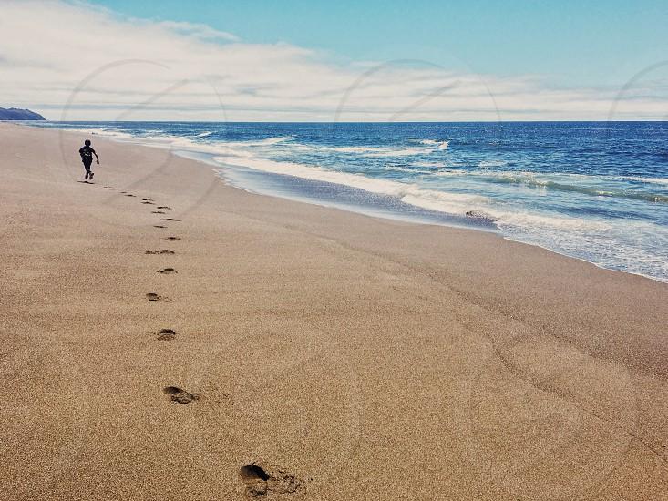 A boy running across a beach.  photo