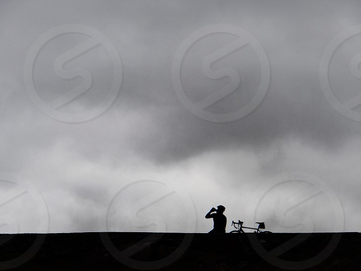 silhouette of person beside bicycle under gray sky photo