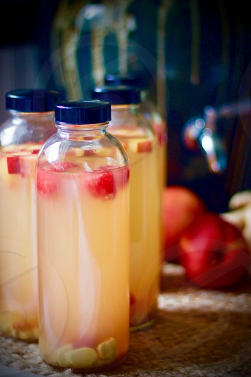 Health & Wellness - Kombucha bottled for a second-ferment flavored with nectarines raspberries and ginger root slices on a natural fiber mat whole nectarines and raspberries in a paper carton stoneware kombucha crock with a stainless steel spigot in the background photo