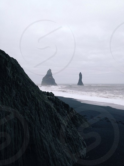 Rock formations in the ocean near a beach in Iceland. photo