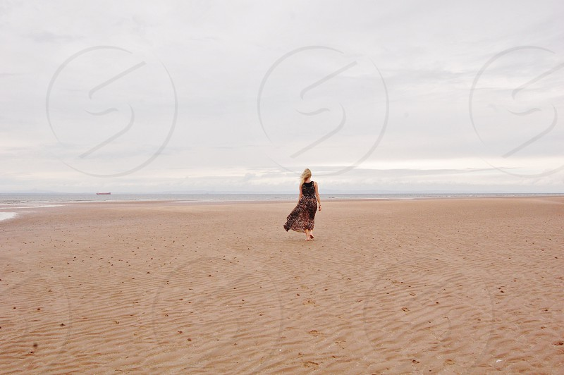 woman wearing brown dress standing on brown sand under white clouds photo