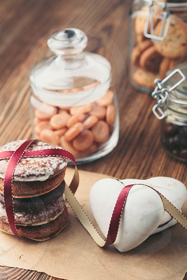Gingerbread cookies candies cakes sweets in jars on wooden table. Portrait orientation photo