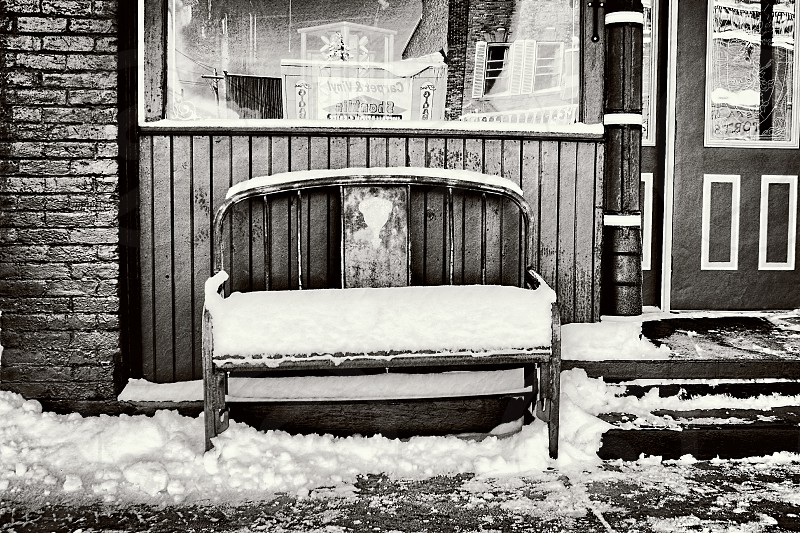 Snow -covered bench on a town's street photo