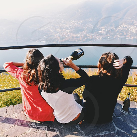 girl in pink sweater sitting next to a girl in black and white sweater holding a wine bottle photo