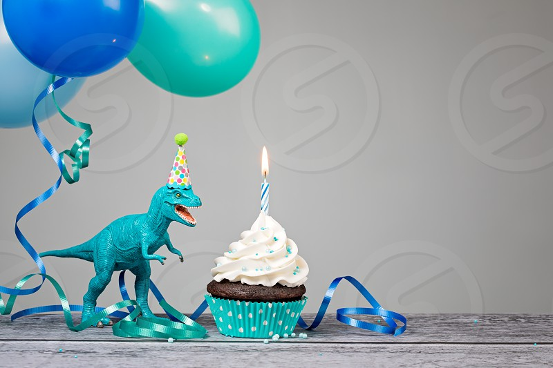 Blue Dinosaur toy with birthday cupcake and balloons on a gray background. photo