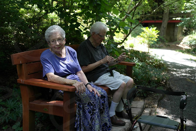 An elderly couple stopping to take a rest on a bench while admiring the scenery in the botanical gardens of the University of North Carolina - Charlotte. photo
