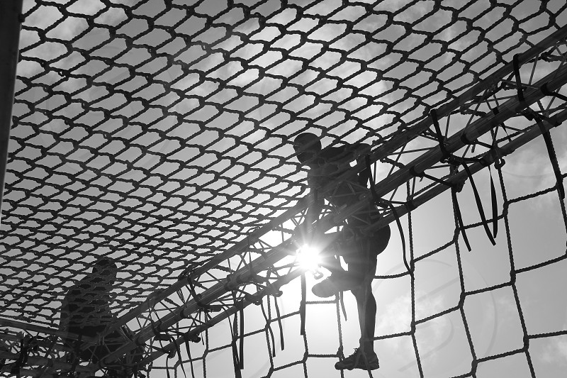 Obstacle course racer conquering obstacles Fearless passion silhouette men runner cargo net climbing racing black and white photo