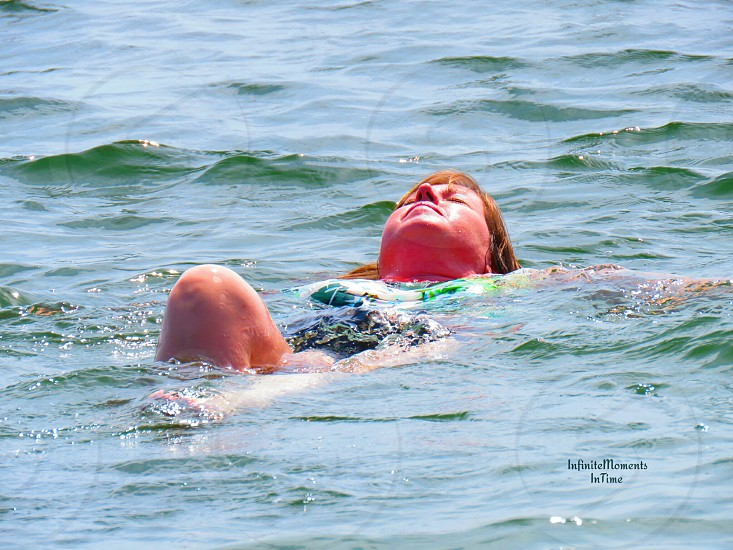 A woman enjoys swimming on a beach in the summer sun. photo